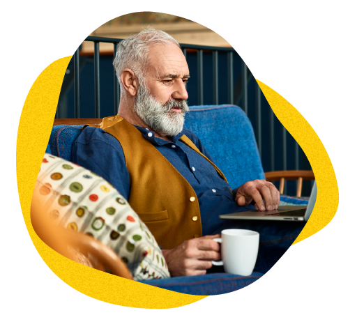 Caucasian man in his 50s with grey hair and beard, participating in a study on his laptop from home while drinking coffee